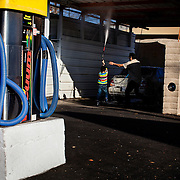 A young boy struggles with a power washer as he helps his father rinse their sedan at a self-serve car wash in Highland Park, California on Sunday, December 22, 2013.