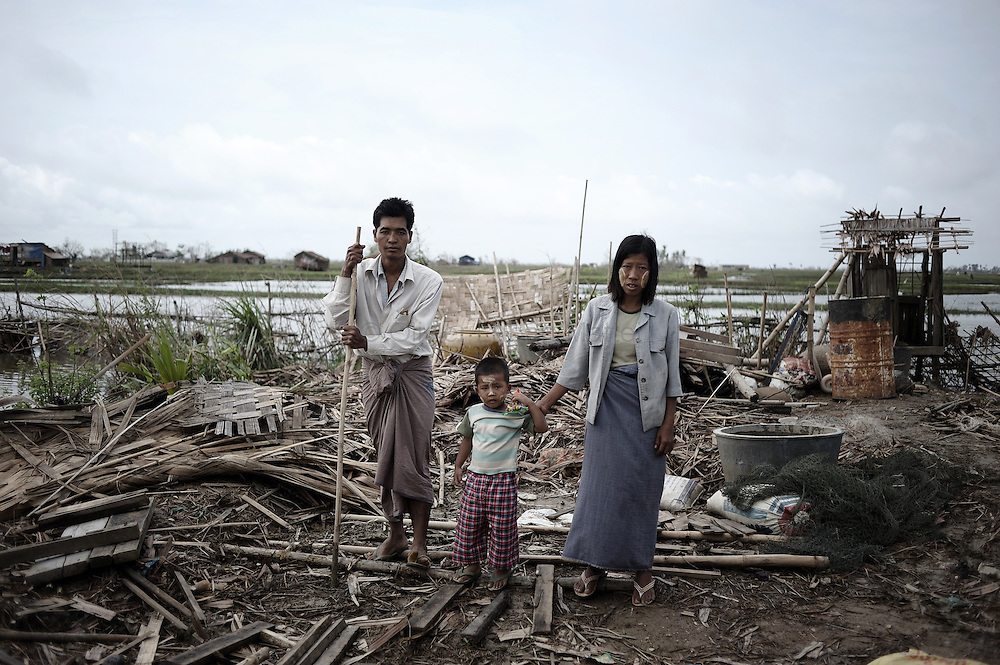 Members of family pose on the debris of their house detroyed by the cyclone Nargis in a village near Kyauktan, in the delta region south of Yangon on May 16, 2008. State television on May 16, 2008 put the latest toll at 77,738 dead and 55,917 missing from Cyclone Nargis, which barrelled into the country on May 2-3, wiping away entire villages and submerging swathes of land under flood waters.