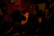 Darko, a Serb who is from Velika Hoca but lives in Germany, has his cigarette lit by a friend during a party on Christmas Eve...Orthodox Christmas (January 7) in the Serbian village of Velika Hoca, Kosovo.