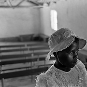 A young girl in her Sunday best waits in a village church for a workshop to begin on the day before she and 60 other girls are to be examined for virginity by a group of mothers in Magqabasini village, near Flagstaff in the former Transkei July 20, 1999.  This tradition has been revived to combat child abuse and high rates of teenage pregnancies and the spread of HIV. (Greg Marinovich)