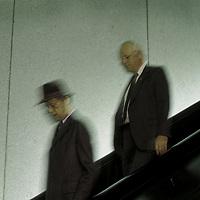 Older men walking down on escalator