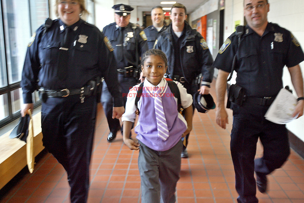 (04/09/10-South Boston,MA) Boston Police recognize 3rg grade student Richard Scott for coming to the aid of a kindergarten student in need of help. On March 29 Paige (NO LAST NAME per school principal), a Tynan Elementary School kindergarten student got lost after dismissal. Richard Scott, on his way home from school, noticed her seeming out of sorts and in need of help. He asked Paige if she was ok and she told him he was lost. He contacted police and stayed with her until all was right. Here, Boston cops from Southie escort him to the ceremony. Staff photo by Mark Garfinkel.