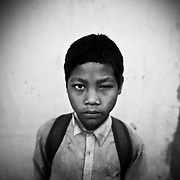 A young Cambodia school boy, his family former Khmer Rouge fighters under Pol Pot, looks on from outside his classroom in Anlong Veng, Cambodia.