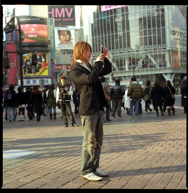 Gal-O boy text messaging on his phone at Hachiko Crossing, Shibuya, Tokyo, Japan.