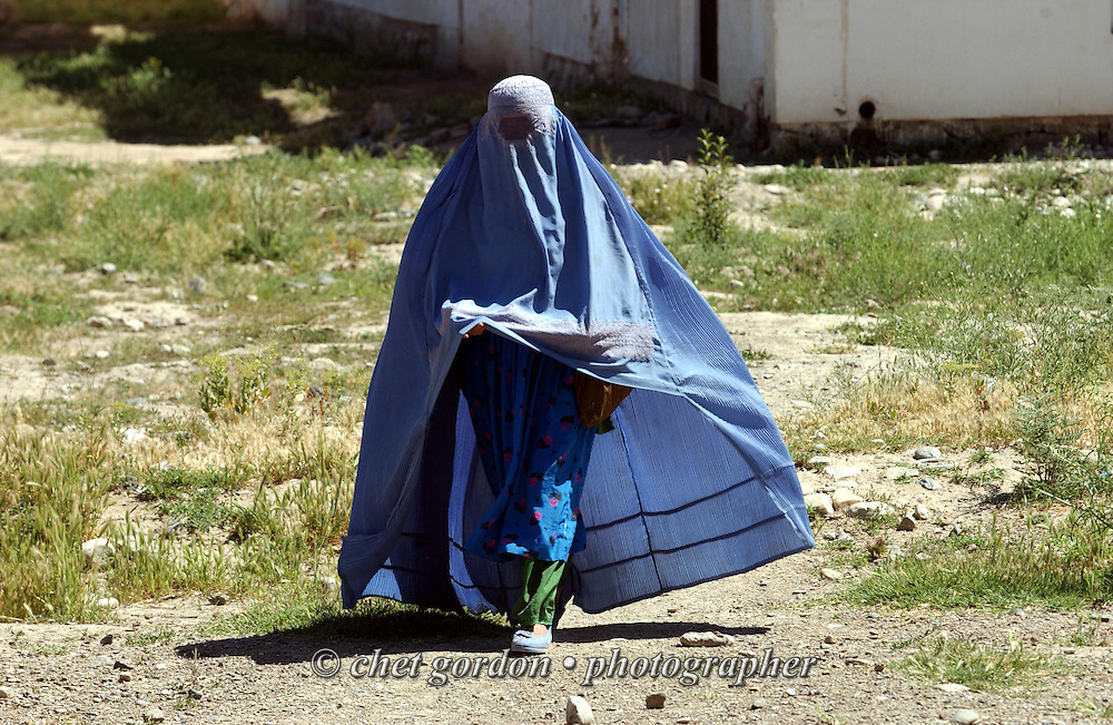 "An Afghan woman dressed in traditional burka leaves the feeding center near the Charasyab health clinic approximately 20 kilometers outside of Kabul, Afghanistan on Sunday, May 26, 2002. The women are taught nutrition, cooking and feeding techniques in a program sponsored by the German NGO, Hammer Forum. A humanitarian mission organized by The Geshundheit Instititute, founded by Dr. Hunter ""Patch"" Adams, Lufthansa Cargo, and DHL Worldwide Express collaborated to ship medicines, food and orthopedic supplies to the Indira Ghandi Children's Hospital, clinics and orphanages in Kabul. Hammer Forum supervised the distribution of the donated supplies from various non-profit organizations in the U.S. and The Netherlands."