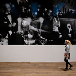 London, UK - 8 October 2012: a woman walks by a picture by William Klein at the Tate Modern exhibition 'William Klein + Daido Moriyama'. The exhibition examine the relationship between the work of William Klein (b.1928) and that of Daido Moriyama (b.1938). Taking as its central theme the cities of New York and Tokyo, the show explores both artists' celebrated depictions of modern urban life.
