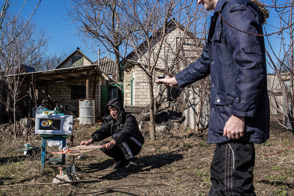 LUHANSK, UKRAINE - MARCH 16, 2015: Pavel Pavlov, left, holds lightbulbs over a microwave-emitting device dubbed the Magnetron as Aleksandr Kryukov, right, films in the yard of the house where Kryukov lives with his grandmother in Luhansk, Ukraine. The two have created a series of popular YouTube videos involving scientific experiements. CREDIT: Brendan Hoffman for The New York Times