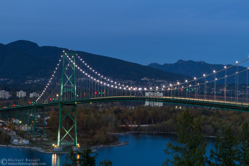 Rush hour traffic crosses the Lions Gate Bridge from Stanley Park in Vancouver, British Columbia to North Vancouver in the early evening. Photographed from Prospect Point in Stanley Park with Mount Seymour and Mount Fromme in the background.