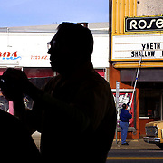 A customer gets a haircut at the Roseway Barber Shop while across the street Bob Kane changes the sign at the Roseway Theater.  Residents from the Roseway neighborhood conducted their own city planning process which they hope will make their area more pedestrian friendly.