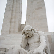 The Male mourner sculpture in front of the twin white pylons of the ‪Canadian National Vimy Memorial‬ dedicated to the memory of Canadian Expeditionary Force members killed in World War one. The monument is situated at a 100 hectare preserved battlefield with wartime tunnels, trenches, craters and unexploded munitions. The memorial designed by Walter Seymour Allward opened in 1936.