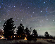The Big and Little Dippers over Quailway Cottage near Portal, Arizona, as the Big Dipper rises in the northeast, with all but the end star of the handle visible. Polaris is at upper left, and the Little Dipper hangs down from it. Airglow adds the green streaks at right. <br /> <br /> This is a blend of 4 tracked exposures for the sky and 4 untracked exposures for the ground, blended along the tree line, as a sharp mask dividing earth and sky was not possible. In fact for the ground shots the camera was moved down to include more of the ground, as the 35mm lens used here wasn&rsquo;t quite wide enough to include all the scene in one frame. So this is a small vertical panorama. Each exposure was 2 minutes at f/2 and at ISO 1600. Plus an additional shot taken thru the Kenko Softon filter was layered in for the star glows. Shot Dec 10, on the last clear night of a fine week-long run of shooting.