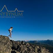girl hiker jumping across sharp rocks, montana, badger two medicine area,  montana, russel country, montana, usa, russell