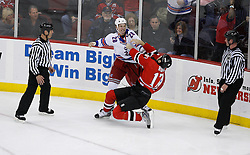 Feb 9, 2009; Newark, NJ, USA; New Jersey Devils left wing Mike Rupp (17) gets knocked down by New York Rangers right wing Colton Orr (28) during the second period at the Prudential Center.
