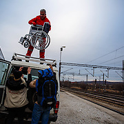 Aide workers load a wheelchair onto a Red Cross SUV, to be taken to the Serbian border along with the chair's owner, Khalid, 55, a refugee who fled Iraq to Syria during the Gulf War, and now is a refugee for a seond time. Tabanovce transit center, Macedonia, January 2016.