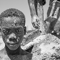 Madagascar, Morondova, Portrait of young man covered in mud while laboring in primitive brick works