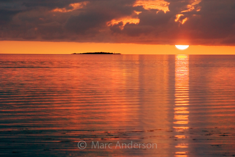 A sunset and clouds over a tiny island in the Fiji archipelago..