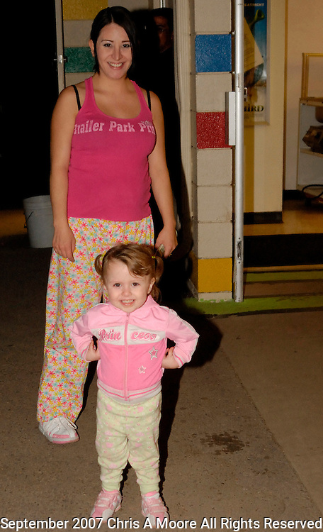 Mother & daughter in their matching outfits pose outside the snack bar at Cinderella Twin.