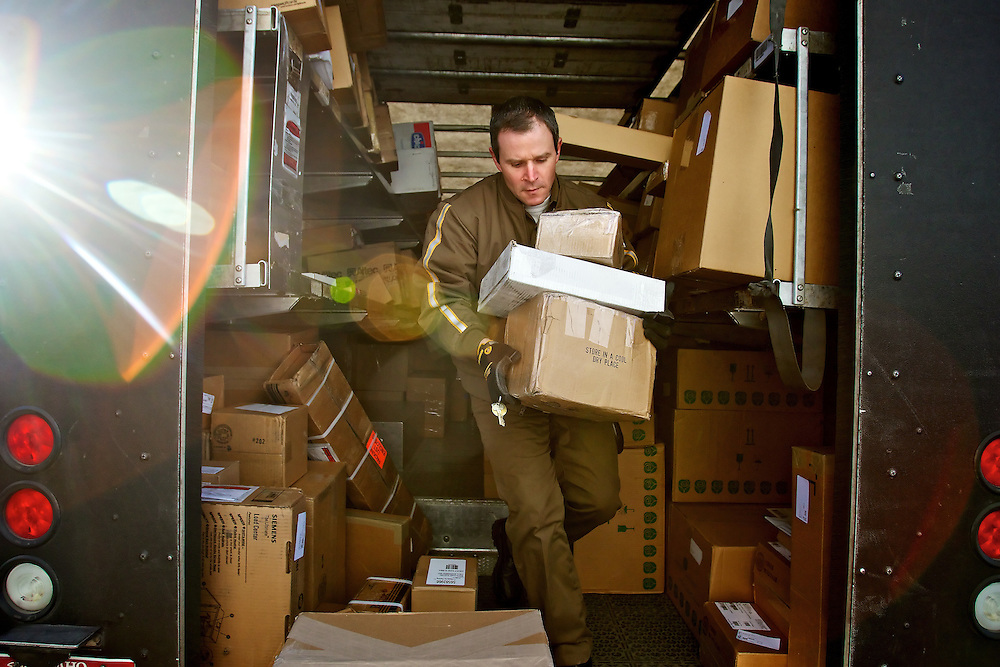 Tony Caldero, a UPS driver in Coeur d'Alene, carries packages from inside his delivery truck Tuesday during his morning route. Caldero, an Army veteran and UPS employee for the past 20 years, has one of the few careers left that don't require a college degree, provide benefits at no cost to the employee and offer a pension after 25 years of employment.