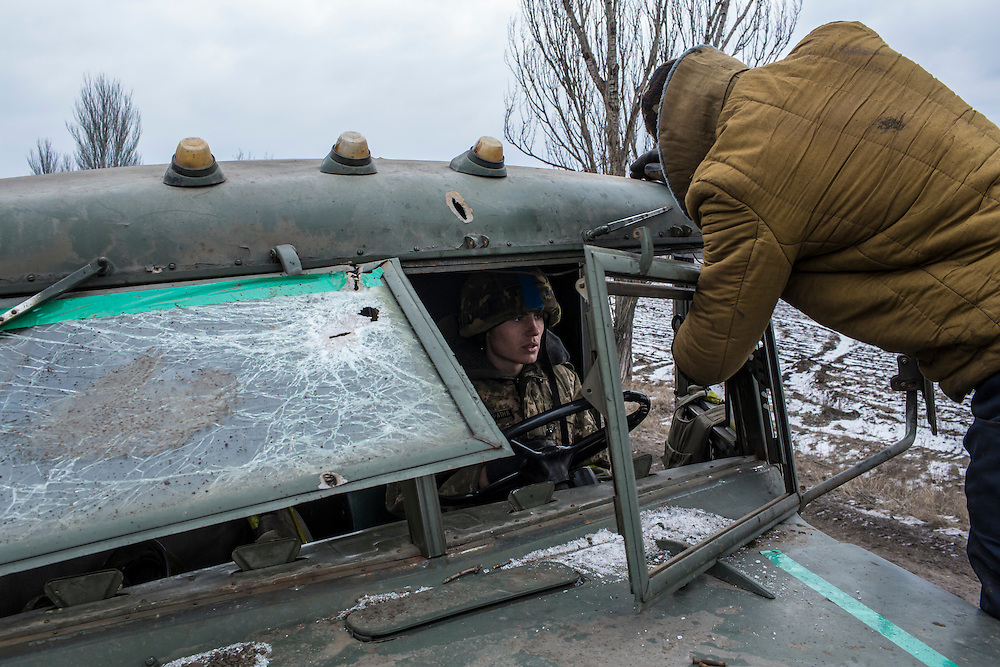 ARTEMIVSK, UKRAINE - FEBRUARY 19: Ukrainian soldiers from a unit based in Zaporizhia repair the bullet-shattered windshield of a truck after taking fire during their withdrawal from Debaltseve the previous day on February 19, 2015 in Artemivsk, Ukraine. Ukrainian forces started withdrawing from the strategic and hard-fought town of Debaltseve yesterday being effectively surrounded by pro-Russian rebels. (Photo by Brendan Hoffman/Getty Images) *** Local Caption ***