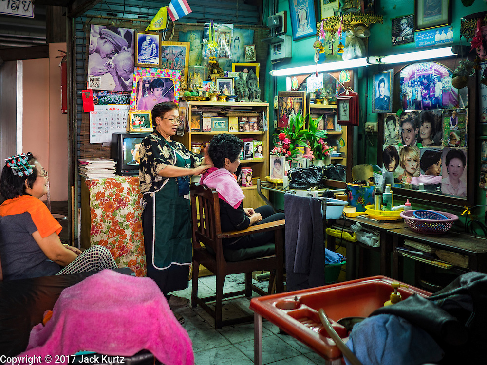 """06 FEBRUARY 2017 - BANGKOK, THAILAND: Woman in a hairdressing shop in what used to be known as Kalabok Market under the Phra Khanong Bridge in the Phra Khanong district of Bangkok. Kalabok is the Thai word for hairdresser and the market was called Kalabok because there were many barbershops and hairdressers under the bridge. In 1985, the city changed the name of the market to """"Singha Market."""" There are still about 10 small men's barbershops, most with just one barber, and four women's salons, most with one hairdresser,  under the bridge.      PHOTO BY JACK KURTZ"""