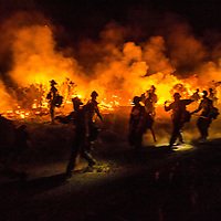 Fire crews hike with chainsaws, axes, and pulaskis along a firing operation at the Border Fire in San Diego County, June 23rd, 2016. Firing operations are designed to ignite brush in front of the main fire on firefighter's terms, depriving the main body of fire fuel when it reaches the burned area from the firing operation.<br /> <br /> The firing operation was massive and risky, but was a last-ditch effort to save the tiny town of Campo near the Mexican border. Luckily weather conditions improved and the firing operation saved much of the town. <br /> <br /> The Border Fire burns near Campo and Potrero Wednesday in San Diego County, CA. The fire was 15% contained and had burned approximately 6,500 acres. <br /> <br /> Long exposure image