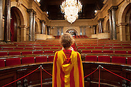 A catalan woman wearing the independence flag, is inside the Catalonian Parliament in Barcelona. Every year the people of Catalonia celebrates the Independence Day on 11th September, when Catalonia troops where defeated by the army of Spain at the Siege of Barcelona in 1714. 300 hundreds years later, in 2013, Catalonian people commemorates this date protesting peacefully and claiming the independence with a human chain, called the Via Catalana, of around 400.000 persons, spreaded 400km along the whole catalonian land.