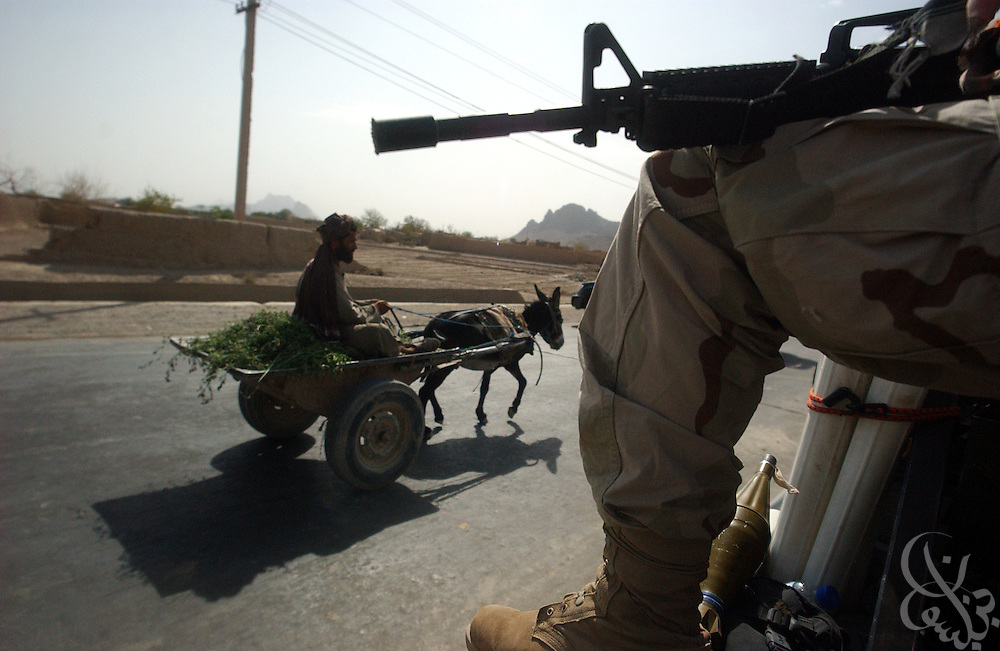 An Afghan man on a donkey cart is passed by US troops riding in a convoy along the road to Kandahar, Afghanistan July 21, 2002, .