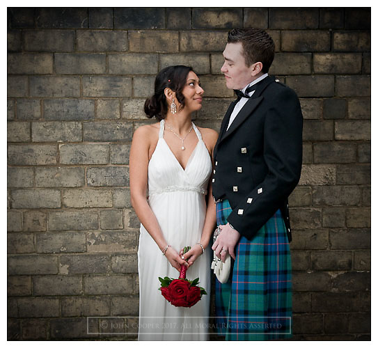 Portrait of Bride and Groom at brick wall.