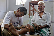 In one of the many marriage halls that are being used as tempory accommadation Ranjan's face contorts as he practices the art of hand healing on 65 yr old Vellayar. Hand healing is used to help ease both physical as well as emotional pain. Vellayar injured himself trying to save his grandson when the tsunami struck, his grandson was one of the thousands of children that died in Nagapattinum district.