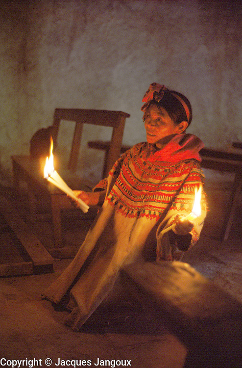 Indian woman praying holding candles in church of San Mateo Ixtatan, Cuchumatanes Mountains, Guatemala