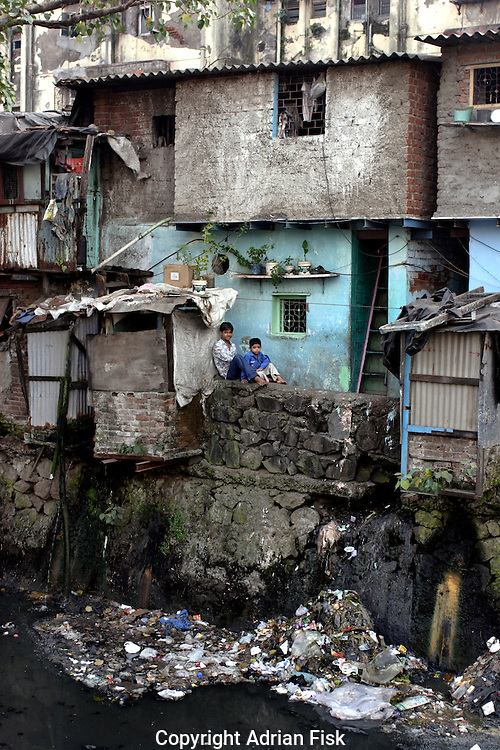 Two boys look up from outside their home on 21st Oct 2006. The water flowing past acts as the drainage system for the slum and is highly polluted.
