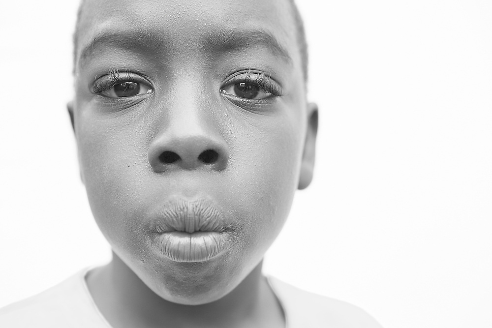 Black and white close up portrait photograph of unhappy African American kid
