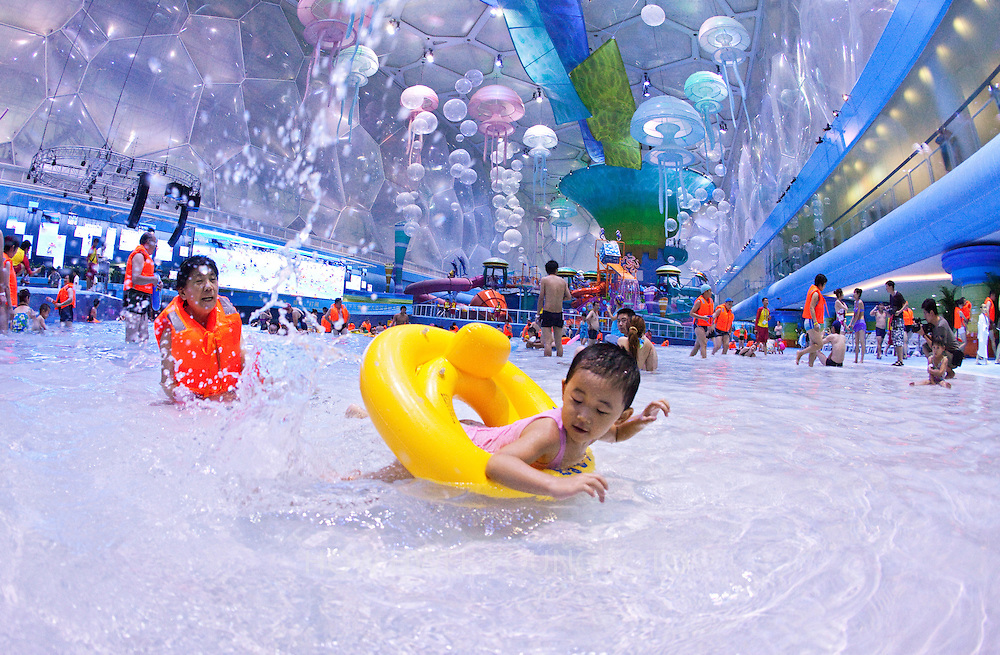 epa02277626 A picture released on 08 August 2010 of visitors enjoying the wave pool during a media preview of the new water park at the National Aquatics Center, better known as the Water Cube, in Beijing, China on 07 August 2010. Built alongside the Beijing National Stadium on the Olympic Green for the swimming competitions of the 2008 Summer Olympics, the water cube opens on 08 August 2010 as Asia's largest indoor water park to coincide with the two-year anniversary of the start of the Beijing Olympics. Operators are hoping that the water park with its seven-storey slides, a wave machine, shopping arcades, cafes and performance stages, will pull in new crowds for the venue after it was closed for a 10-month reconstruction.  EPA/HOW HWEE YOUNG