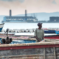 A man and pelican look in opposite directions in Old Harbour Bay, as a coal-burning plant spews smoke in the background