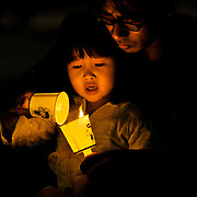 A girl lights her candle off of her father's candle during a nightime demonstration against the government of President Lee Myung-bak and the import of US beef in Seoul, South Korea.