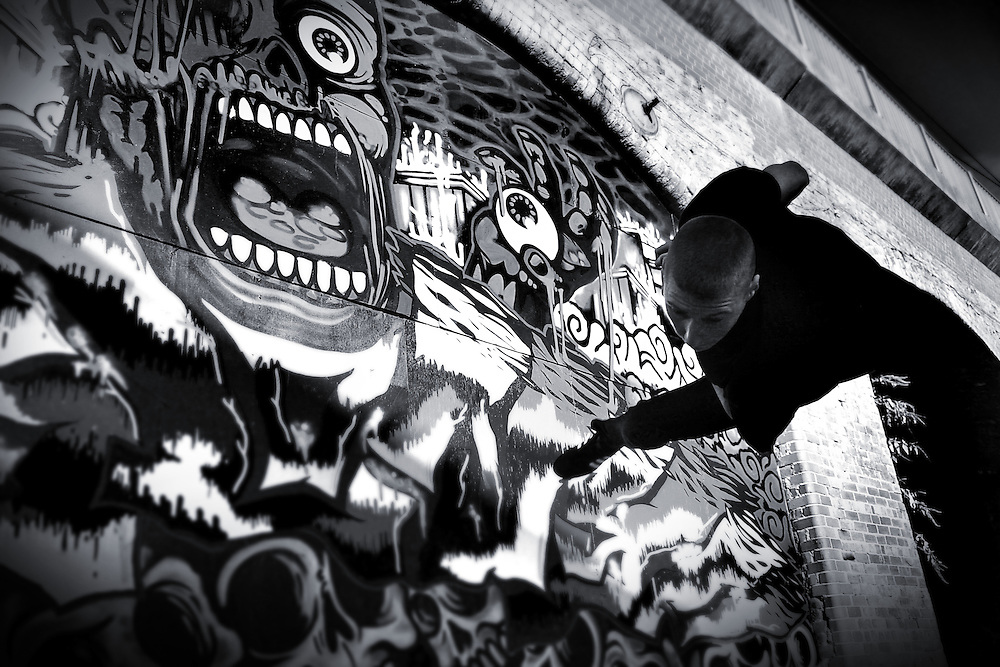 Black and White image of free runner Jack (Jakk) Lowry performing a cork in front of a large grafitti wall under the train arches in Leeds, UK.