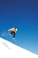An airborne snowboarder inside a half pipe with a blue sky.
