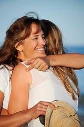 two woman hugging on the beach