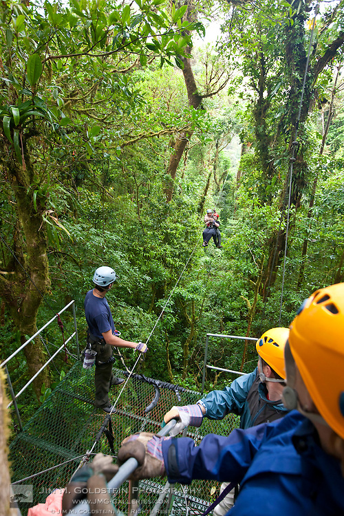 A group of people zip lines through the cloud forest canopy in the Monteverde Cloud Forest Reserve in Selvatura Adventure Park, Costa Rica