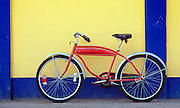 Red cruiser bicyle against blue and yellow wall; Dewey town, Culebra Island, Puerto Rico.