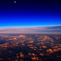 Aerial view of the moon rising over cumulus clouds illuminated by the last rays of the setting sun.