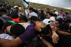 An injured protester is carried up the mountain before being taken away in an ambulance.