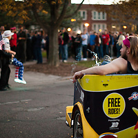 A rickshaw driver looks on at Trump rally supporters at the University of Wisconsin, Eau Claire campus, candidate Donald Trump spoke at the campus on November 1st, 2016