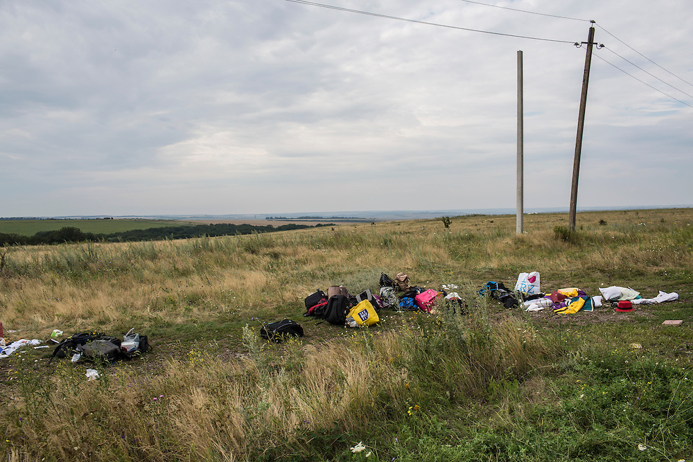 GRABOVO, UKRAINE - JULY 19: Luggage and personal belongings from Malaysia Airlines flight MH 17 lie in a field on July 19, 2014 in Grabovo, Ukraine. Malaysia Airlines flight MH17 was travelling from Amsterdam to Kuala Lumpur when it crashed killing all 298 on board including 80 children. The aircraft was allegedly shot down by a missile and investigations continue over the perpetrators of the attack. (Photo by Brendan Hoffman/Getty Images) *** Local Caption ***