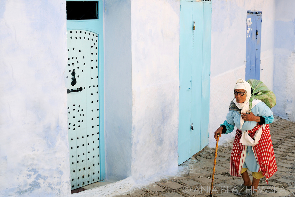 Morocco, Chefchaouen. Older woman, wearing typical Rif Mountains dress walking the streets of the blue medina in Chefchaouen.