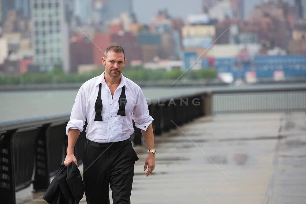 handsome middle aged man in a tuxedo shirt walking on a pier in Hoboken, NJ after a rain storm.