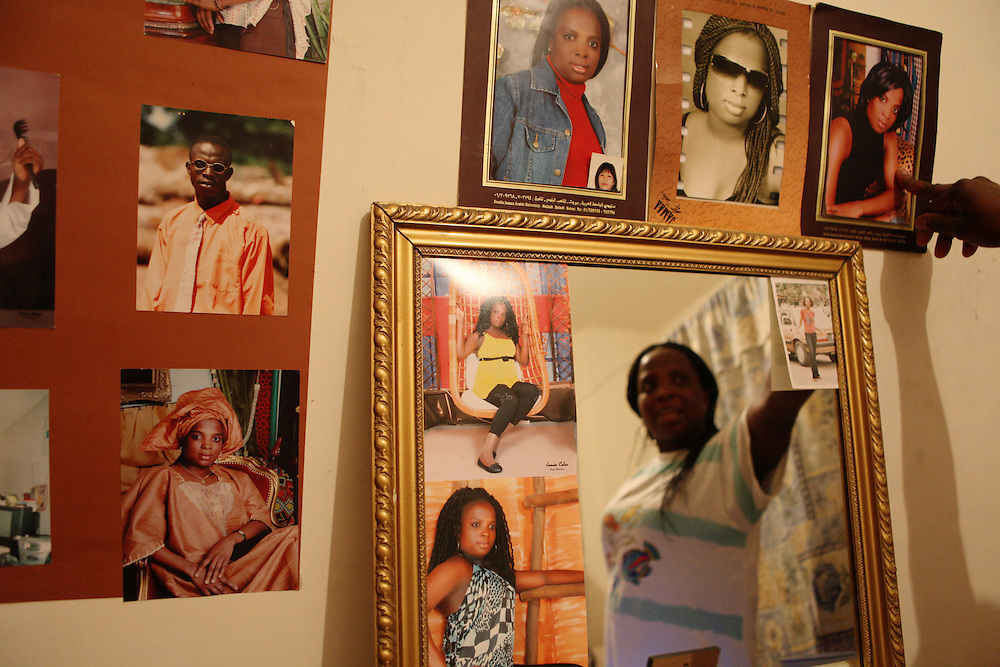 A Nigerian woman in her home points to her favorite photograph of herself.