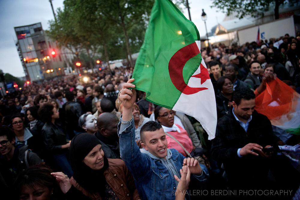 An Algerian family, part of the large African community supporting Hollande, celebrate with the country's flag.