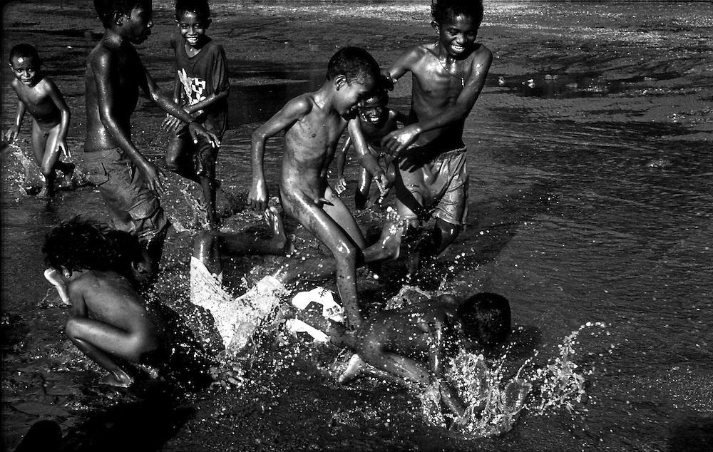Children playing soccer in mud in Metihaut. @ Martine Perret. 17 May 2002