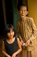 Old woman with her granddaughter at their house in Thanh Ha Village, near Hoi An, Central Vietnam,